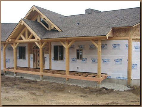 Logs and roofing in place on porch