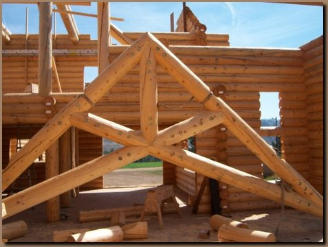 Log Scissor style truss about to be lifted in place